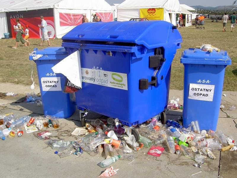 Myslieť ekologicky nestačí - Nepriehliadnuteľné kopy odpadkov pri kontajneroch a vreciach na odpadky.